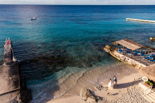 Bride and groom walk barefoot on beach at their destination wedding in Cozumel, Mexico