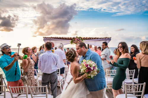Bride and groom kiss while guests cheer during sunset Mexico destination wedding ceremony
