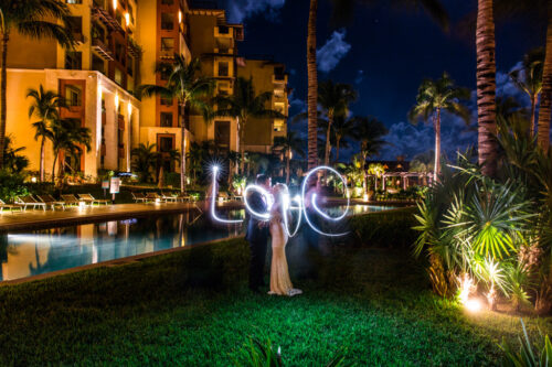 Bride and groom kiss with LOVE lights at their Cancun, Mexico destination wedding