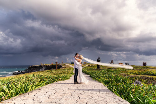 Isla Mujeres destination wedding portrait of bride and groom with veil and stormy sky