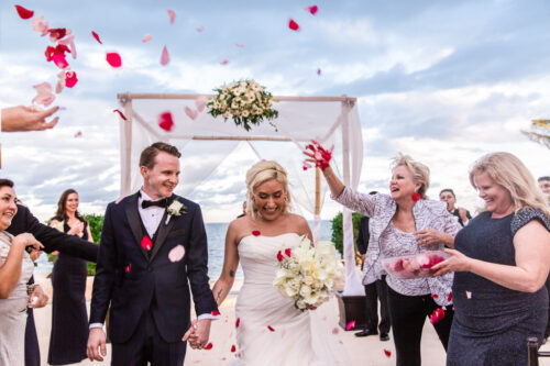 Just married bride and groom walk through rose petal toss at their Cancun destination wedding ceremony in Mexico