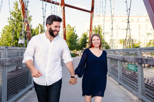 Candid Chicago engagement photo of couple running on 606 path