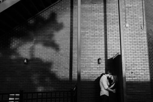 Romantic photo of couple kissing in shadows in Wicker Park Chicago neighborhood