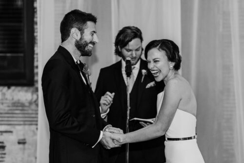 Candid wedding ceremony moment of couple laughing at ARIA Minneapolis event venue