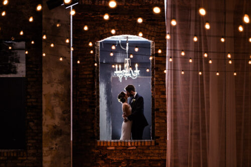 Bride and groom kiss in brick window with string lights at industrial ARIA Minneapolis wedding