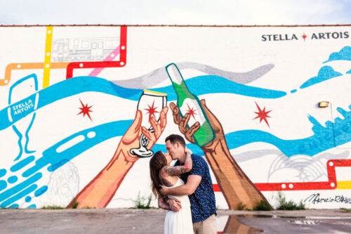 Couple kiss in front of Chicago flag mural during summer Chicago engagement session