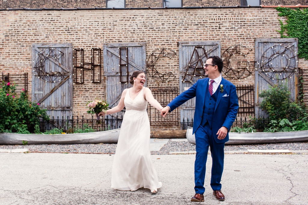Happy bride and groom dance in courtyard of Salvage One wedding venue with CHICAGO sign