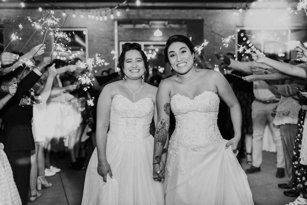 Happy brides smile during sparkler exit at their summer Concord Fifty Five wedding