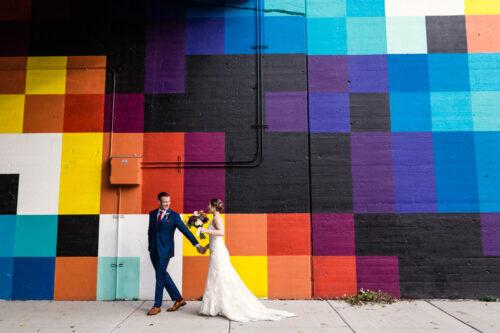 Bride and groom walk along colorful Chicago mural before their West Loop restaurant wedding