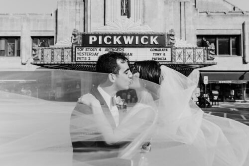 Bride and groom at Pickwick Theatre where they first met with custom wedding day marquee