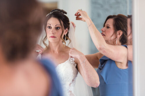 Bride looking in mirror while getting ready for intimate Cheney Mansion wedding