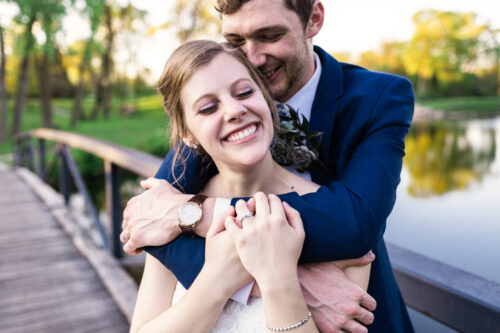 Happy bride and groom on bridge during sunset at their Silver Spring Golf Club wedding