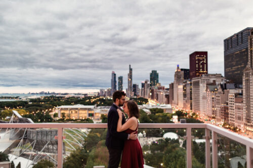 Romantic fall engagement session at downtown Chicago rooftop overlooking city lights at dusk