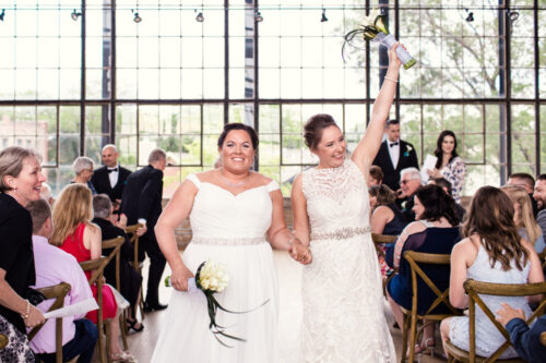 Happy brides walk down the aisle after Ravenswood Event Center wedding ceremony