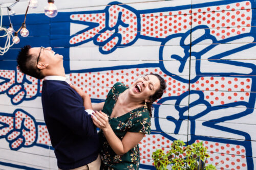 Couple laughing hysterically during food-focused Logan Square engagement session