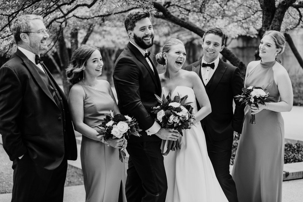 Candid photo of wedding party laughing at Art Institute Garden before Chicago Athletic Association wedding