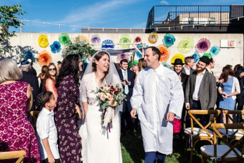 Happy bride and groom exit their Chicago Ignite Glass Studio wedding ceremony