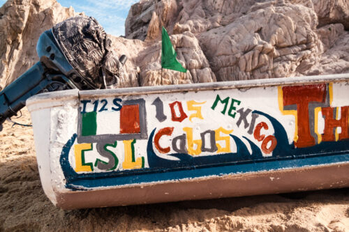 Painted boat on Lovers Beach in Cabo San Lucas, Mexico by travel photographer Emma Mullins Photography