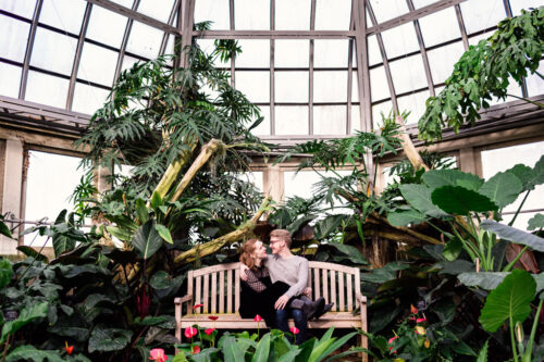 Romantic Garfield Park Conservatory engagement photo of couple on bench with greenery