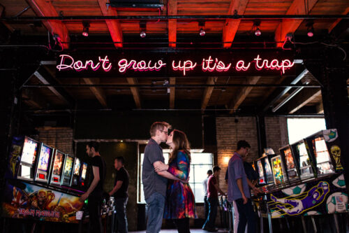 Headquarters Beercade engagement Chicago arcade engagement session with neon sign Don't Grow Up it's a Trap