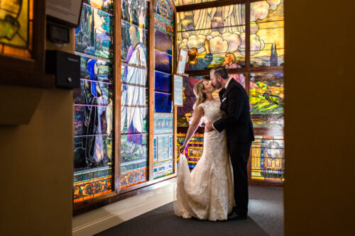 Chicago bride and groom kiss in stained glass gallery at Evanston Halim Time and Glass Museum wedding