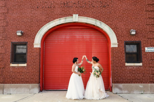 Newlywed Chicago brides dancing outside of their summer Concord Fifty-Five wedding