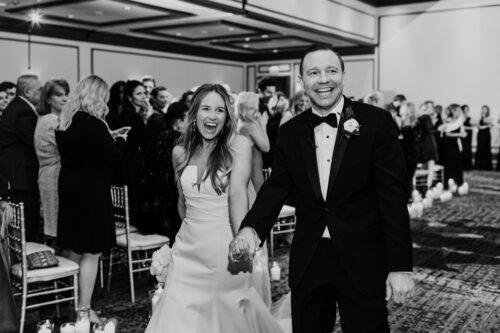 Happy bride and groom walk down aisle at winter Renaissance Chicago wedding