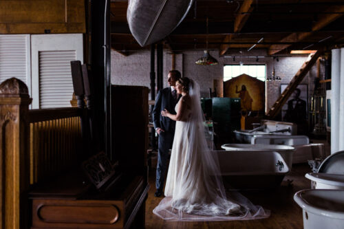 Portrait of bride and groom with canoe and bathtubs at Salvage One wedding venue in Chicago