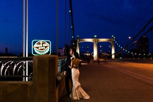 Minneapolis bride and groom on Hennepin Bridge at night with Grain Belt Beer sign