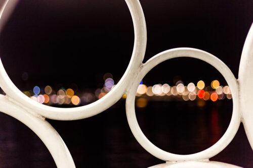 Creative photo of Amsterdam city lights through circle sculpture across IJ River