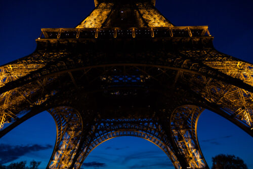 Illuminated base of Eiffel Tower in Paris, France at night