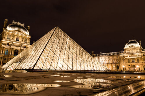 Le Louvre museum in Paris, France illuminated at night after rain