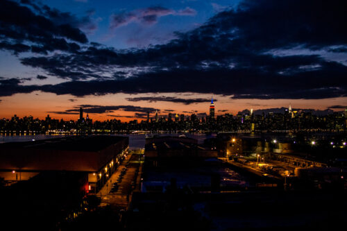 View of New York City skyline at sunset from rooftop in Brooklyn