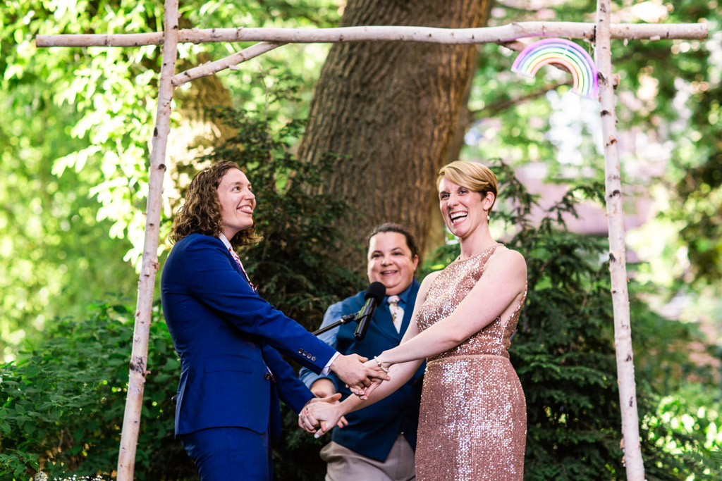 Couple smiles at guests during their summer Firehouse Chicago wedding ceremony
