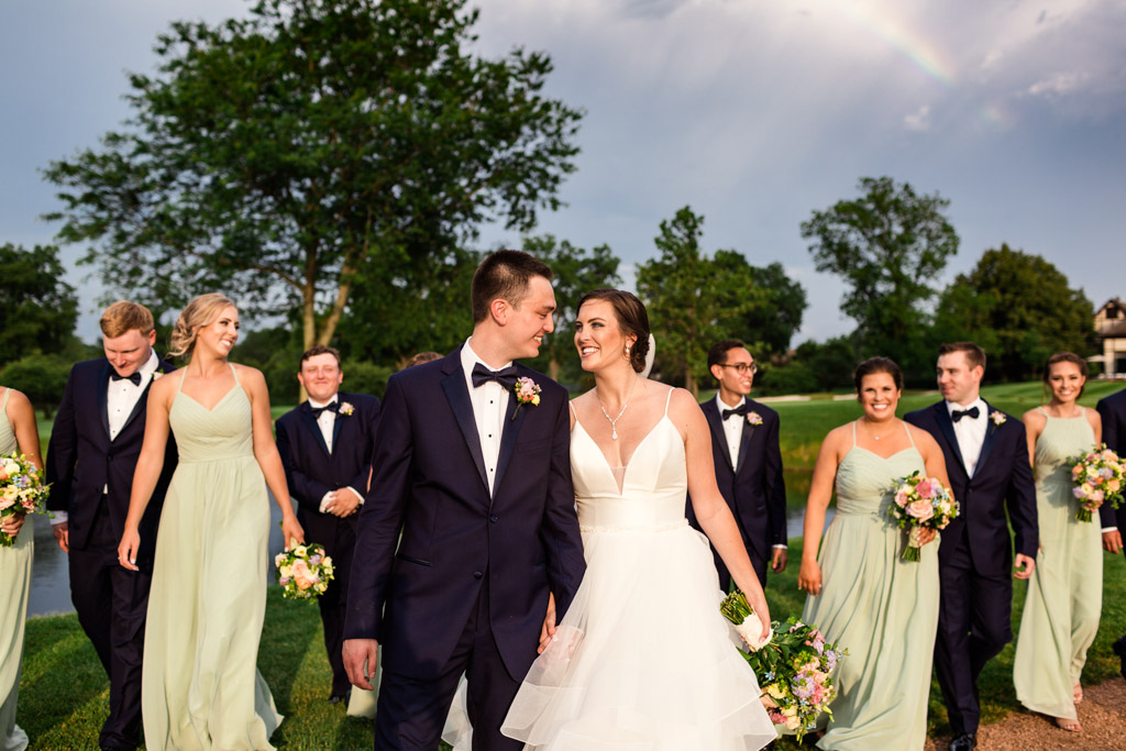 Candid photo of Illinois wedding party walking with bride and groom under rainbow at Sunset Ridge Country Club