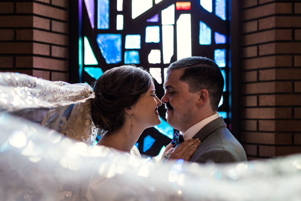 Romantic photo of bride and groom in church with stained glass