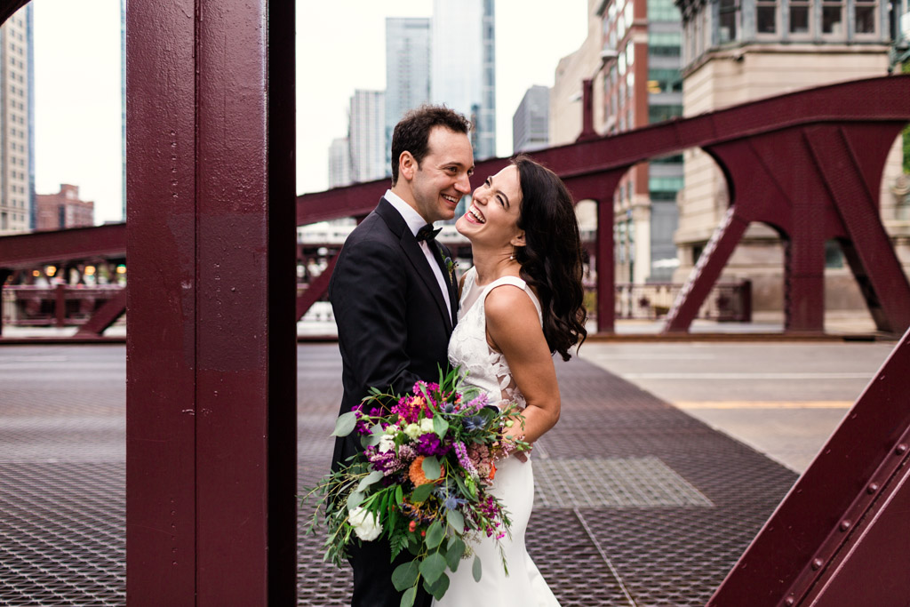 Candid photo of bride and groom laughing on bridge before their Chicago microwedding ceremony