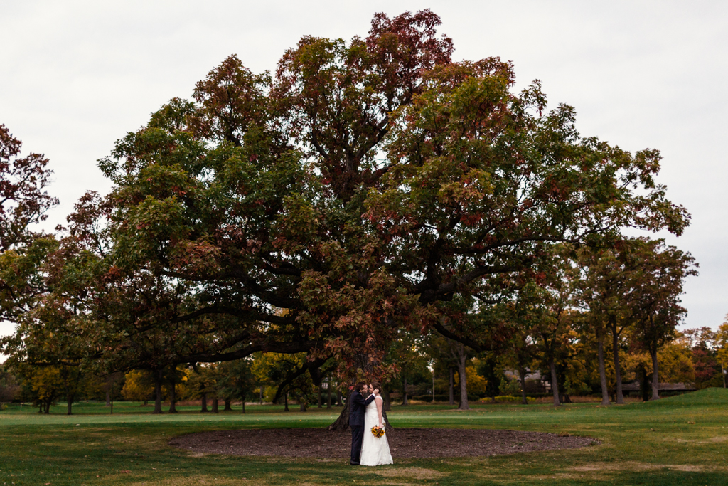 Fall Winnetka wedding photo of bride and groom with Oak tree at Indian Hill Club