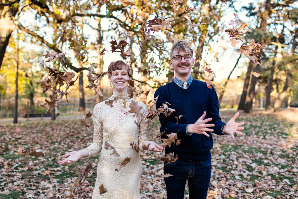 Happy bride and groom toss leaves at their Halloween wedding in Chicago