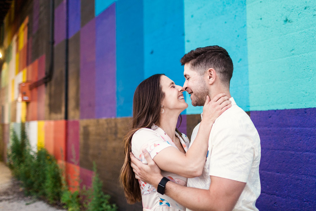 West Loop engagement photo of couple smiling in front of colorful wall